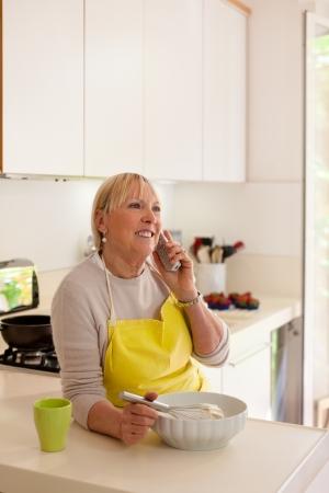 jasschort: Happy senior vrouw thuis, koken in de keuken en praten over de telefoon