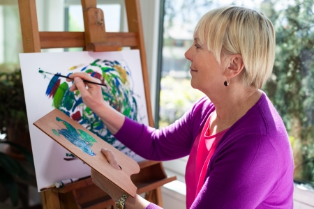artist: Happy retired woman painting on canvas for fun at home