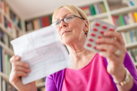 prescription drugs: Elderly caucasian woman with medicine and reading drug prescription. Low angle view Stock Photo