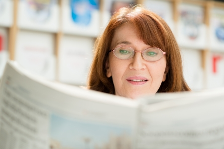 Portrait of middle aged woman with eyeglasses reading paper in library photo