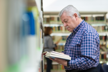 70s adult: Portrait of senior retired man choosing book in library from shelf. Copy space