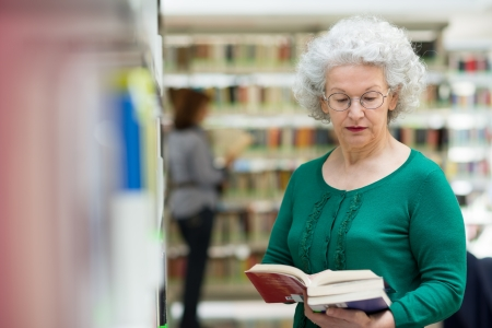 Portrait of old retired woman choosing book in library and taking it from shelf photo