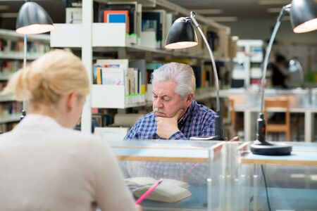 Elderly man studying among young college students in library and taking notes photo