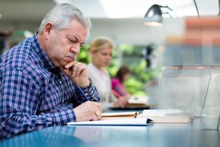 hombre estudiando: Hombre de edad avanzada a estudiar con un grupo de j�venes estudiantes universitarios en la biblioteca y tomar notas