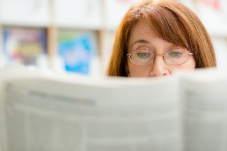 woman reading: Portrait of middle aged woman with eyeglasses reading paper in library