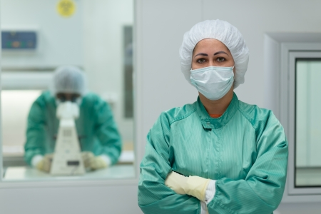 Portrait of woman working in biotechnology research center with man looking through microscope in background photo