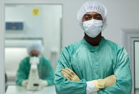 biotecnologia: Retrato de hombre que trabaja en el centro de investigación en biotecnología con la mujer que busca a través del microscopio en el fondo