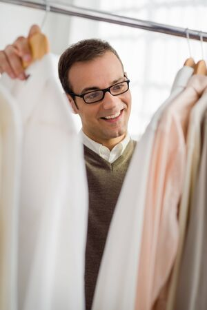 mid adult man shopping for clothes and shirt in fashion store photo
