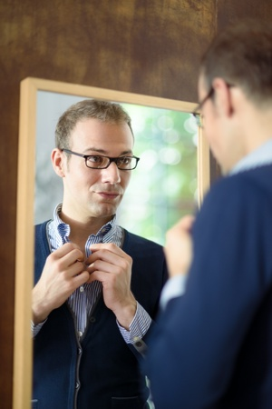 trying on: Portrait of young man with glasses getting ready, dressing up and looking at mirror Stock Photo