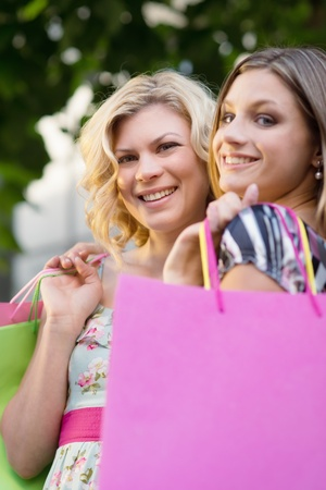 Portrait of two happy young women smiling with shopping bags Stock Photo - 14019535