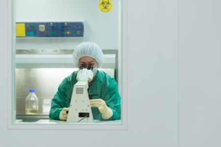 Female researcher working in pharmaceutical industry lab and looking with microscope. Copy space photo
