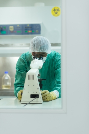 Male researcher working in pharmaceutical industry laboratory and looking with microscope photo