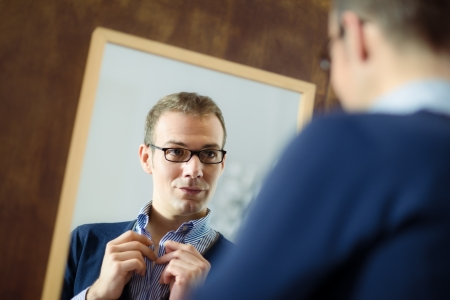 Portrait of young man with glasses getting ready, dressing up and looking at mirror photo