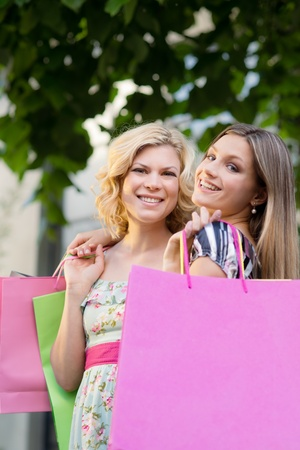 Portrait of two happy young women smiling with shopping bags photo
