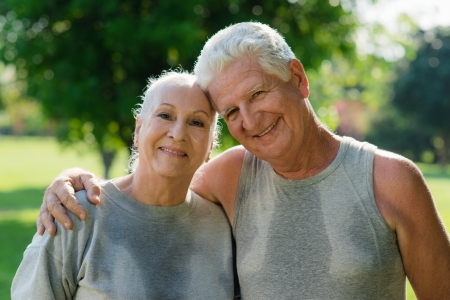 couple exercising: Portrait of happy senior husband and wife after fitness in city park