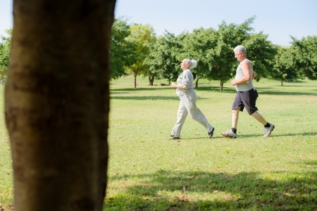 Active retirement, senior couple running and exercising in city park. Copy space Stock Photo - 14122293