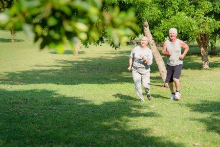 Active retirement, senior couple running and exercising in city park. Copy space photo