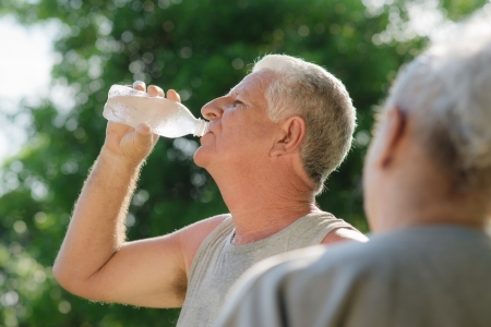 Senior people, old man and woman talking and drinking water after exercising in park photo