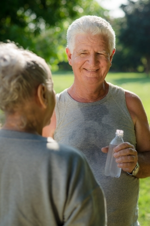 Senior people, old man and woman talking and drinking water after exercising in park Stock Photo - 14122289