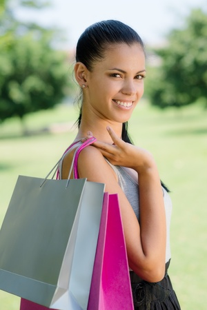 Consumerism, portrait of happy young woman smiling with shopping bags Stock Photo - 14122299
