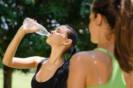sudando: Dos amigas relajarse y agua potable después de correr en el parque de la ciudad Foto de archivo