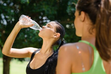 sweating: Two female friends relax and drinking water after running in city park