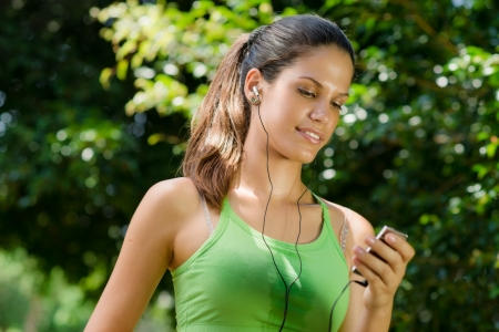 earbud: Young woman with mp3 player doing fitness in city park