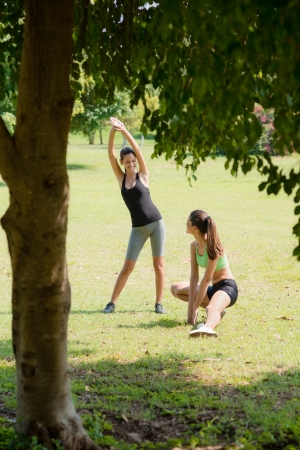 Two beautiful women stretching in city park after running and sport activity photo