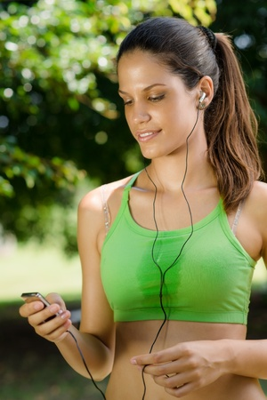 Young woman with mp3 player doing fitness in city park Stock Photo - 14122306