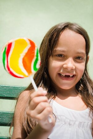 Portrait of cute little girl with candy smiling and looking at camera photo
