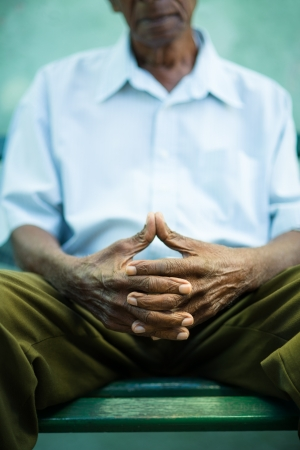 contemplation: closeup of hands of elderly african american man sitting on bench