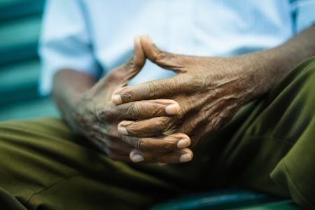 persona deprimida: Primer plano de las manos de los ancianos hombre afroamericano sentado en el banco