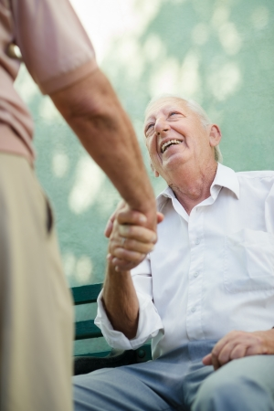 Active retirement, two old male friends talking and shaking\ hands on bench in public park