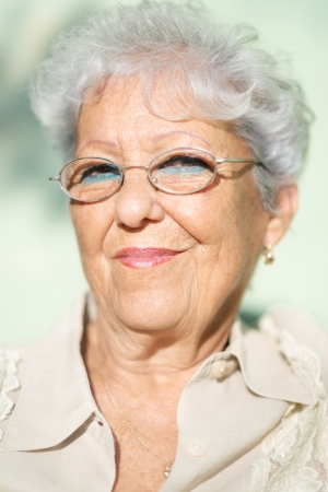 Portrait of senior caucasian woman with glasses looking at camera and smiling photo