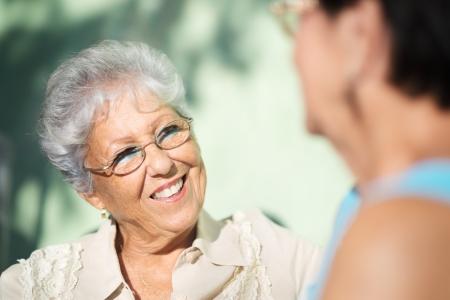 dialogo: Jubilaci�n activa, dos amigas de edad avanzada que habla en banco en el parque p�blico