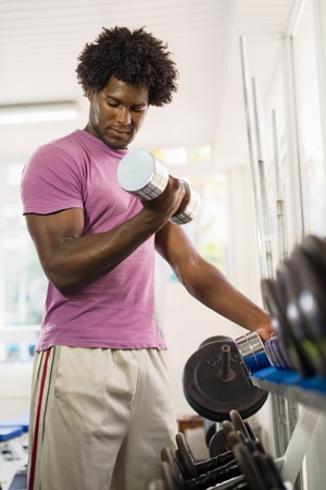 Sport and fun, young african american male athlete taking weights from shelf in fitness club photo