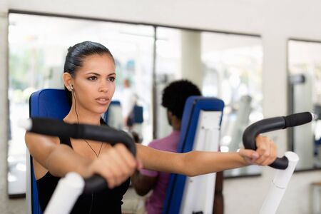 men exercising: Sports activity, young man and woman exercising and working out in fitness gym