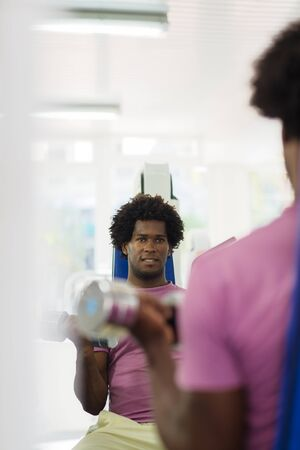 Sports activity, young african man exercising and working out in fitness gym. Copy space photo