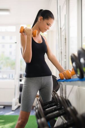Sports and fun, young female caucasian athlete taking weights from shelf in fitness gym photo