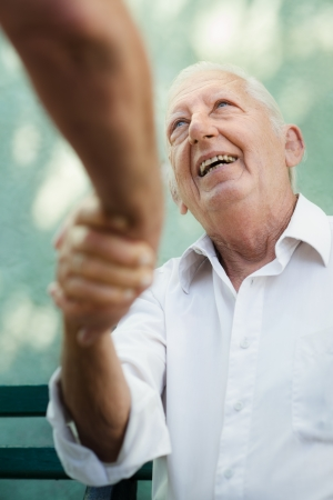 Active retirement, two old male friends talking and shaking hands on bench in public park photo