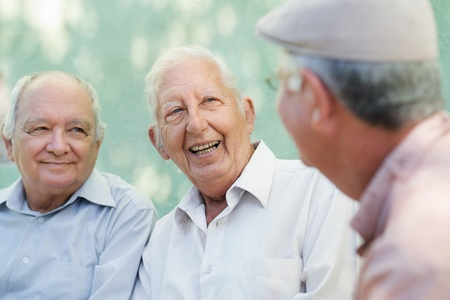 amigas conversando: Jubilación activa, un grupo de tres amigos hombres viejos hablando y riendo en el banquillo en el parque público