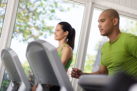 Man and woman working out and running on treadmill in fitness club photo