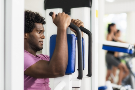 Young black man exercising pectoral muscles in fitness club, with people working out on cyclette in background Stock Photo