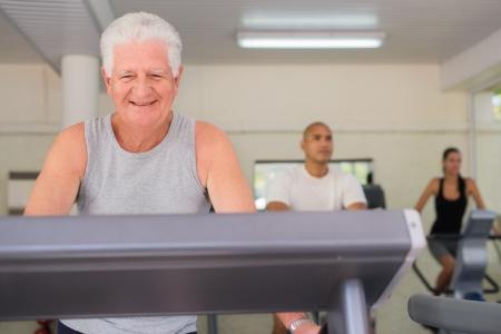 man working out: La gente y el deporte, hombre de edad trabajando en la cinta en el gimnasio de fitness entre los j�venes