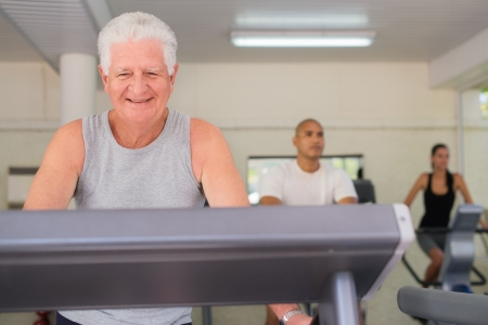 People and sports, elderly man working out on treadmill in fitness gym among young people Stock Photo