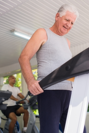 man working out: People and sports, elderly man working out on treadmill in fitness gym Stock Photo