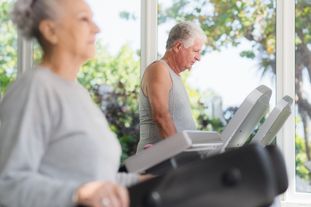 couple exercising: People and sports, elderly couple working out on treadmill in fitness gym Stock Photo
