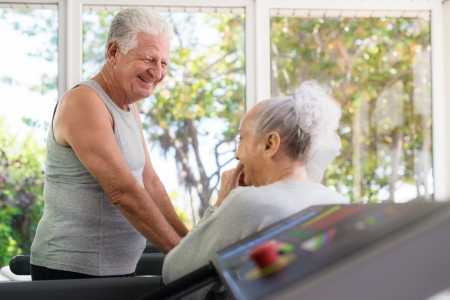 Active retired people, old man and woman talking and exercising in fitness gym photo
