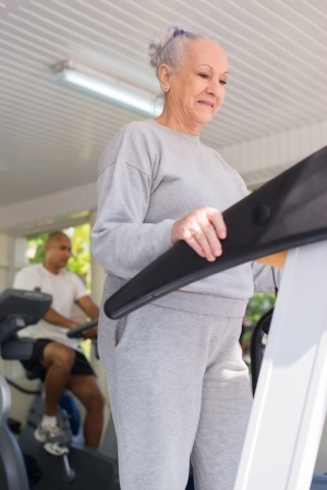 senior exercising: People and sports, elderly woman working out on treadmill in fitness gym Stock Photo