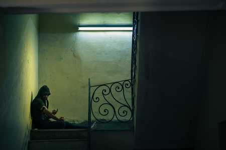 drogadicto: Los asuntos sociales y el abuso de drogas, joven inyectando hero�na y sentado en las escaleras. Copie el espacio